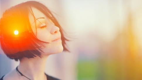 Eine Frau sieht bewusst aus, in ihrem Kopf leuchtet die Sonne