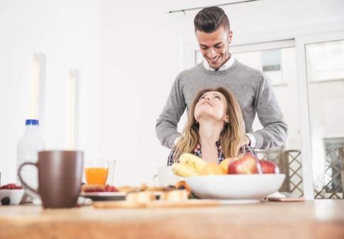 Ein Mann massiert seiner Partnerin die Schultern, während sie am Frühstückstisch sitzt.