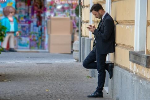 Ein Mann lehnt gedankenverloren an einer Wand und starrt auf sein Handy.