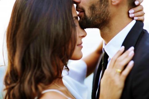 Mann gibt Frau einen Kuss auf die Stirn