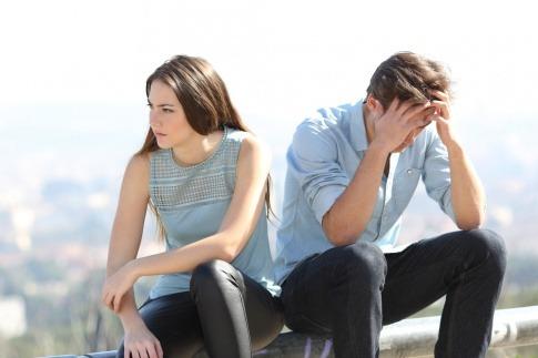 Ein Paar sitzt nebeneinander und macht den Eindruckt, dass die Beziehung scheitert