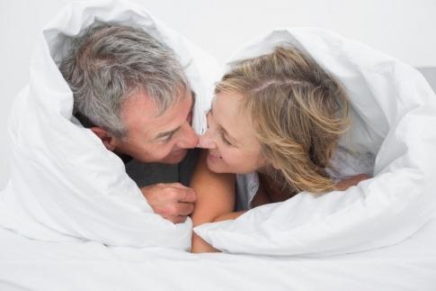Ein Mann und eine Frau in den Wechseljahren im Bett