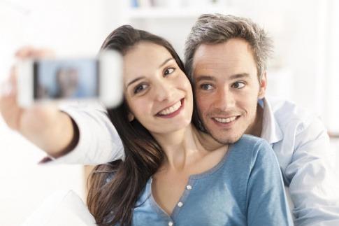 Ein Paar nimmt ein gemeinsames Selfie auf, während es auf einem Sofa sitzt.