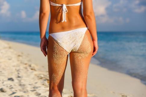 Eine Frau mit Bikinifigur geht am Strand