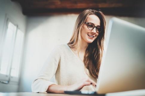 Eine Frau hat bei der Bildschirmarbeit eine Brille auf
