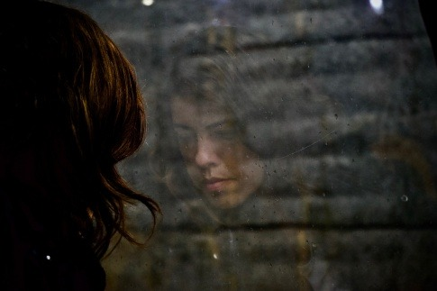 Eine Frau betrachtet ihr Spiegelbild im Fenster. Sie wirkt traurig und ratlos, vielleicht fragt sie sich: bin ich gut genug?