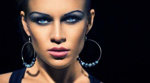 Eine Frau hat mit blauem Lidschatten Smokey Eyes geschminkt