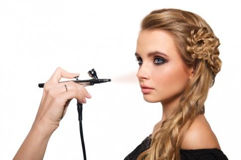 Eine blonde Frau bekommt ein Airbrush Make-up