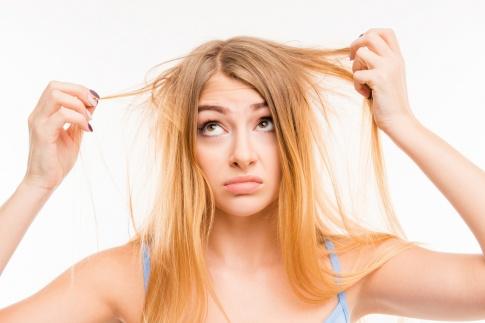 Eine Frau hält Strähnen ihrer blonden Haare in der Hand und schaut verzweifelt. Die Haare sehen sehr trocken aus.