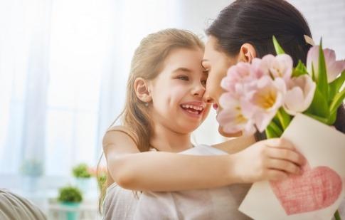 Eine Mädchen überreicht ihrer Mama Blumen und eine Grußkarte