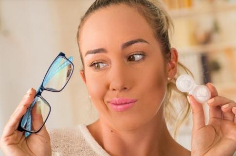 Eine Frau hat Brille und Kontaktlinsen in der Hand