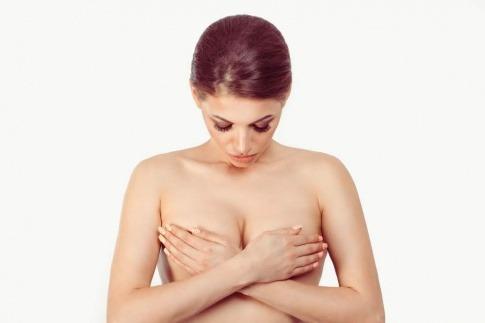 Eine Frau betrachtet ihre hängenden Brüste