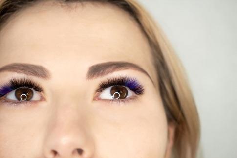 Eine Frau trägt künstliche Wimpern mit bläulichem Farbverlauf