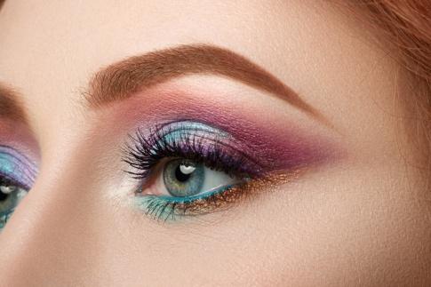 Das Auge einer Frau ist in bunten Farben geschminkt
