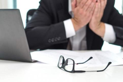 Mann kurz vorm Burnout am Schreibtisch