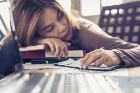 Eine Frau liegt am Schreibtisch wegen Burnout