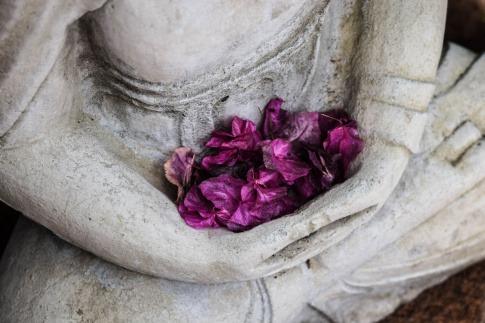 Buddha Statue mit Blüten als Zeichen für Kinderwunsch