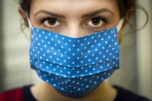 Eine Frau hat eine Maske gegen Corona und scheint Angst zu haben
