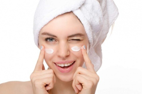 Eine Frau gibt sich Creme statt Botox ins Gesicht