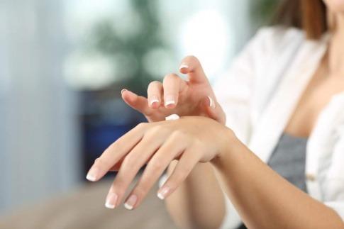 Eine Frau verwendet Creme gegen trockene Hände