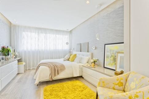 Ein Wohnzimmer wurde mit gelben Akzenten und Glasgegenständen dekoriert