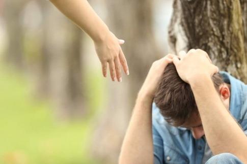 Eine Hand reicht zu einem depressiven Partner