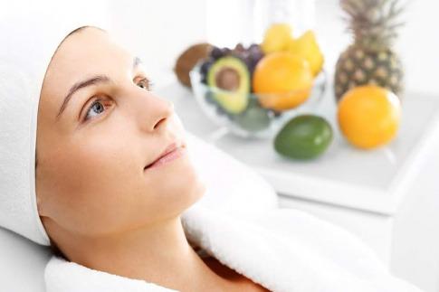 Frau mit Handtuch am Kopf und im Hintergrund frisches Obst
