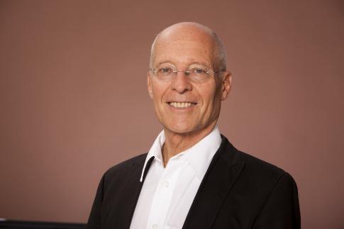 Dr. Ruediger Dahlke sitzt und lächelt
