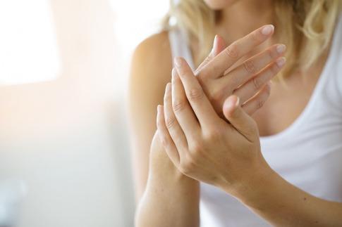 Eine Frau reibt ihre Hände wegen der Durchblutung
