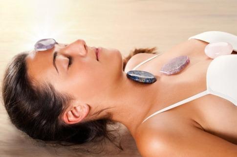 Eine Frau unterzieht sich einer Energiebehandlung. Sie liegt auf einer Liege, dabei sind mehrere Heilsteine und Edelsteine auf ihrem Körper platziert.