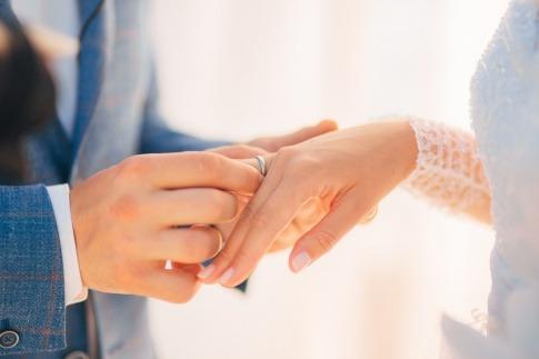Ein Mann steckt einer Frau einen Ehering auf den Finger
