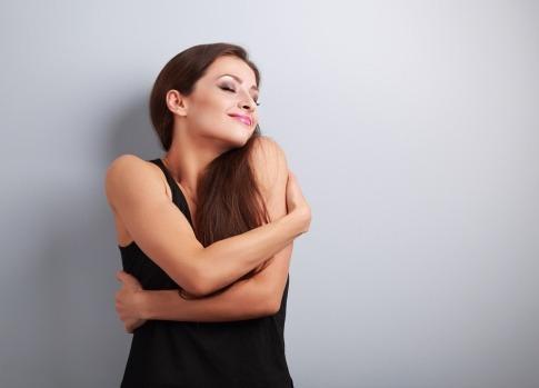 Eine Frau umarmt sich selbst und scheint, den eigenen Körper zu lieben