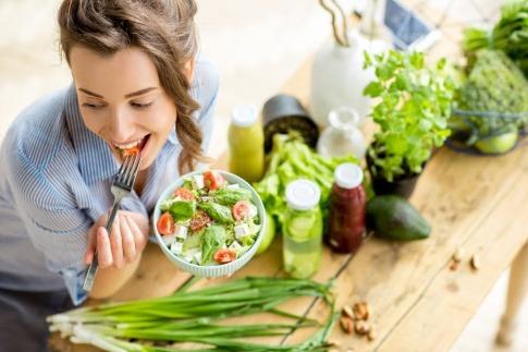 Eine Frau isst einen Salat.
