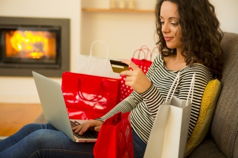 Eine Frau mit Kaufsucht sitzt am Sofa mit vielen Einkaufstaschen und bestellt mit Kreditkarte