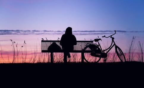 Ein Mann sitzt auf einer Anhöhe alleine auf einer Bank und hat offensichtlich keine Lust auf Menschen.