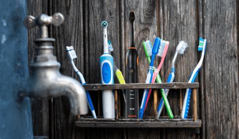 Auf einem Brett stehen elektrische Zahnbürsten und normale
