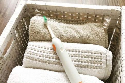 Eine elektrische Zahnbürste liegt in einem Wäschekorb zum Reinigen