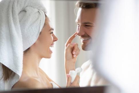 Frau gibt Mann mit empfindlicher Haut Creme mit Feuchtigkeit