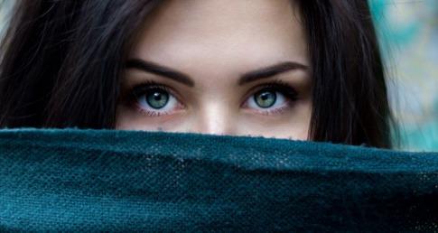 Frau mit sensibler Haut versteckt ihr Gesicht hinter einem Schal