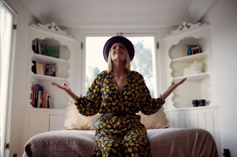 Eine Frau sitzt freudig in ihrer energetisch eingerichteten Wohnung
