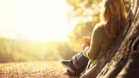 Eine Frau sitzt entspannt an einen Baum gelehnt