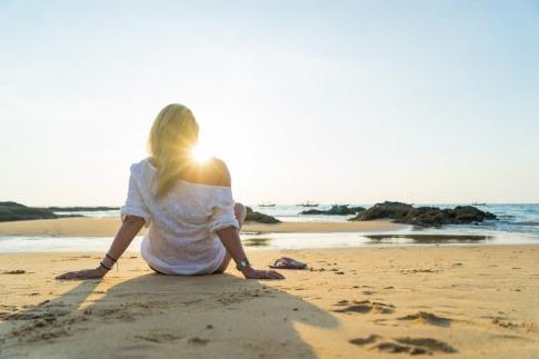 Eine Frau sitzt entspannt am Meer