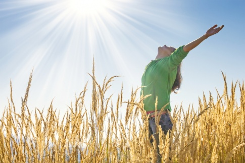 Eine Frau in einem Feld und wirkt befreit