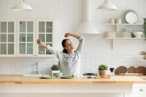 Eine Frau in der Küche wirkt entspannt und glücklich