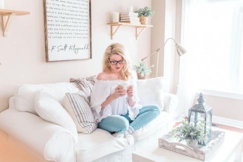 Eine Frau sitzt zuhause entspannt am Sofa