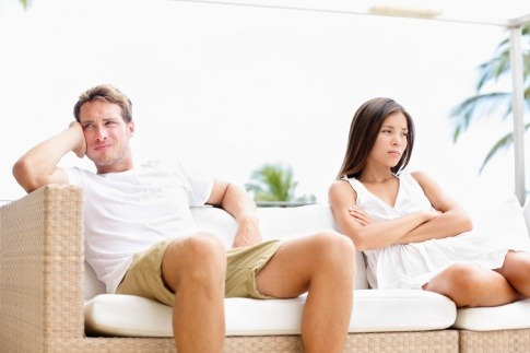 Ein Paar sitzt auf der Couch. Er will nicht, sie will ihren Mann verführen