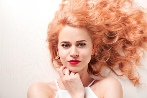 Eine Frau im Freien mit welligen erdbeerblonden Haaren trägt einen roten Lippenstift