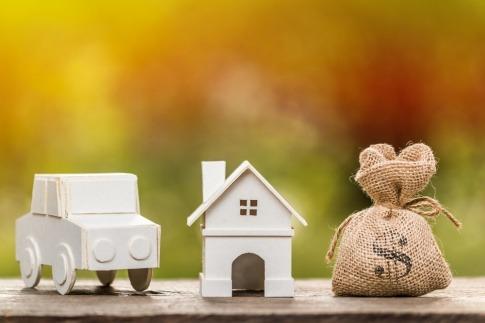 Ein Haus, ein Auto und ein Sack mit Geld stehen als Zeichen für Erfolg nebeneinander