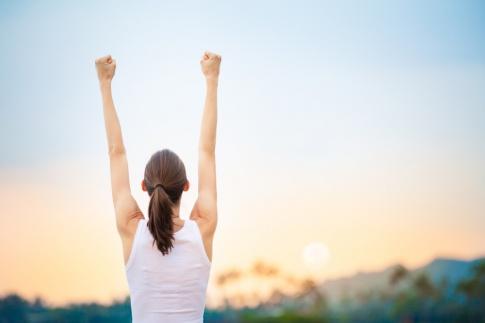Eine Frau streckt erfolgreich die Arme in die Höhe
