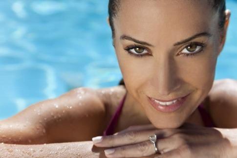 Frau ist im Pool als Erfrischung für die Haut